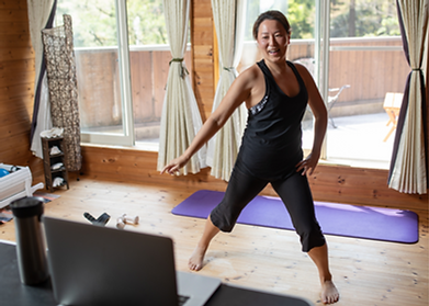 Middle aged woman doing online pilates