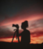 silhouette-of-woman-holding-camera-at-ni