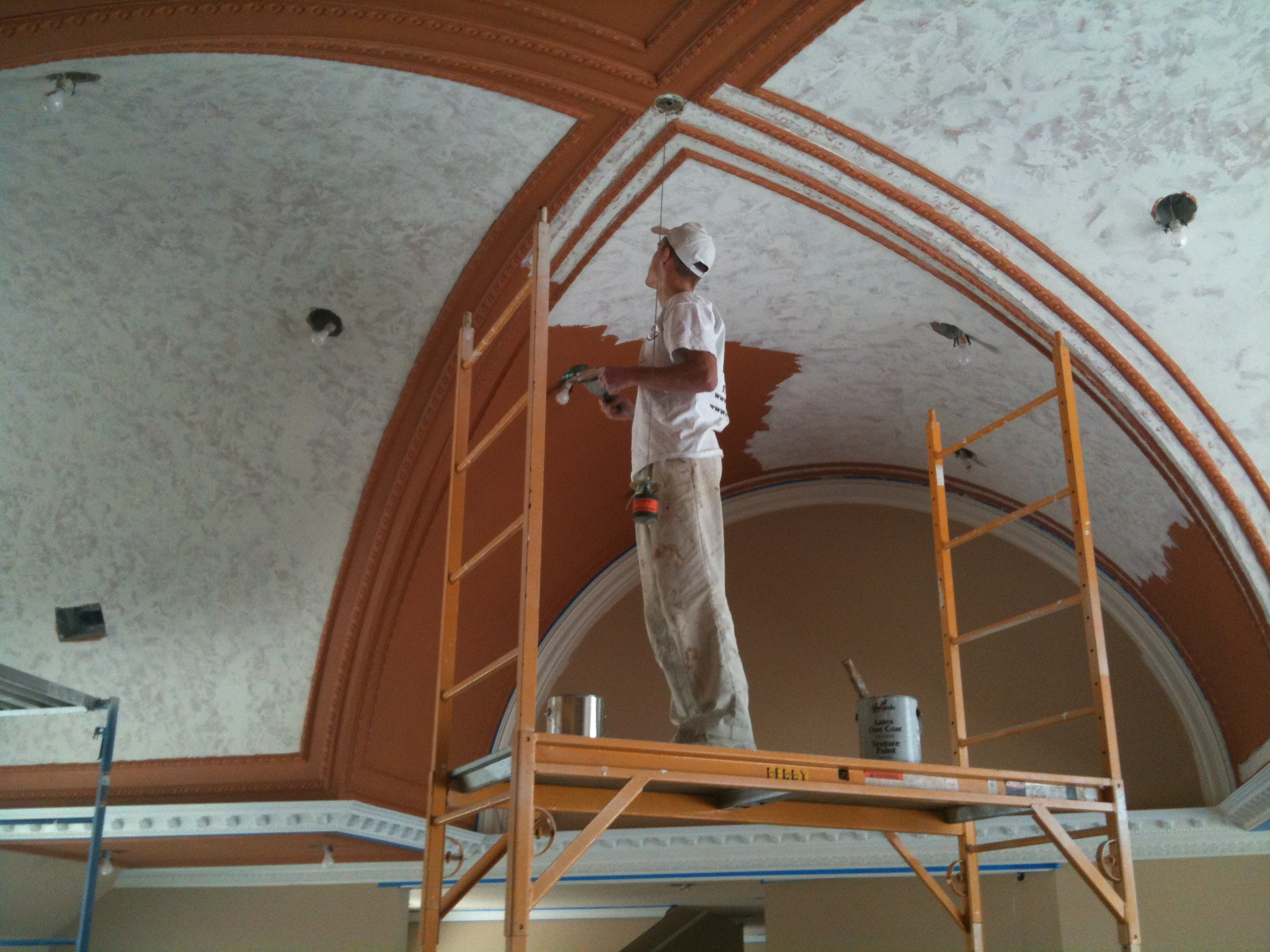 painting high ceiling on scaffold