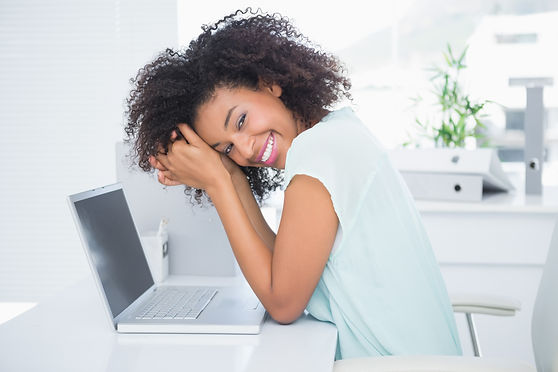 curly haired black woman at desk - happy