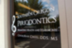 "Front door with text ""Southern Oregon Periodontics, Promoting Health & Harmony, Chun-Han Chou, DDS, MS"
