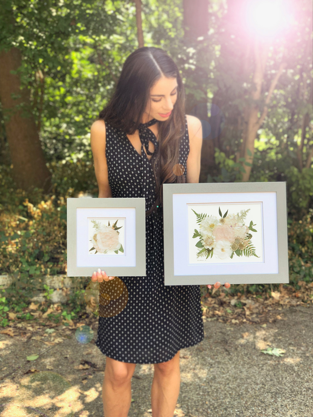 Founder and designer, Andrea Castaneda holding two framed bridal bouquet pieces.
