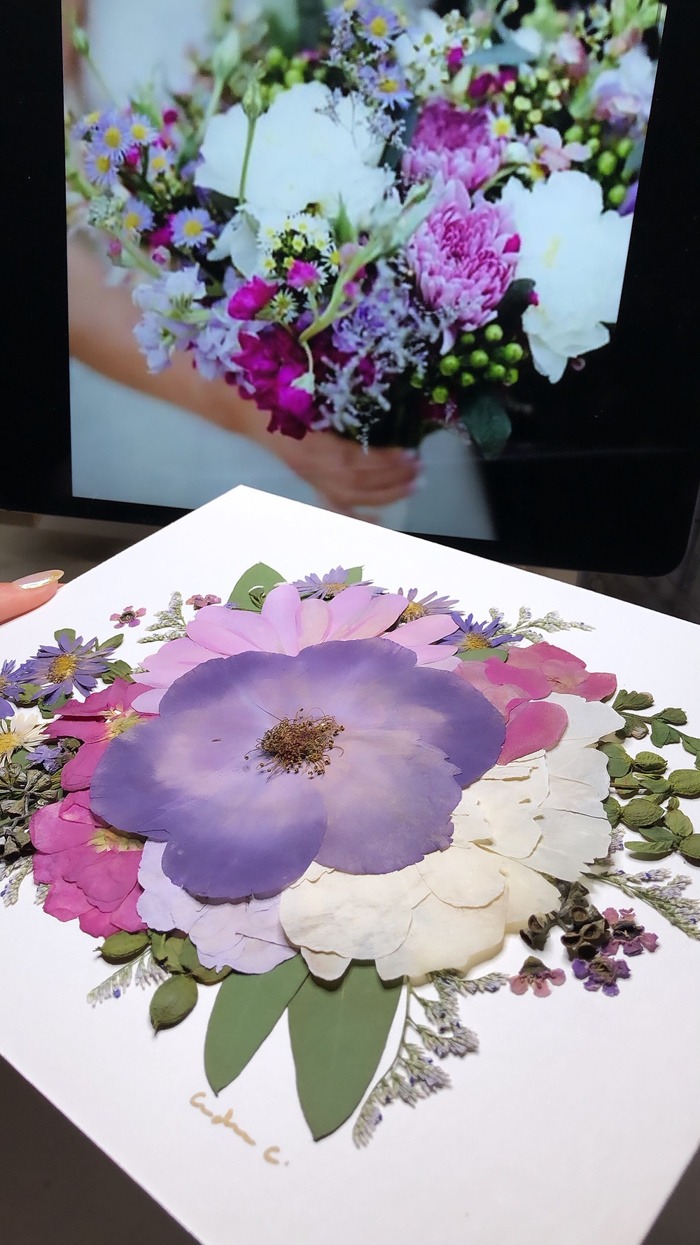 Color-enhanced pressed flower piece next to the original bridal bouquet.