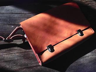 Dark Leather Messenger Bag On Wood