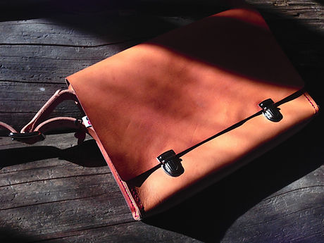 Dark Leather Messenger Bag On Wood
