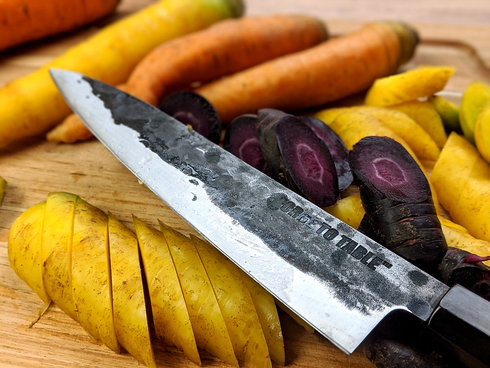 A Forge To Table Gyuto positioned next to a bunch of sliced and whole multicolored carrots