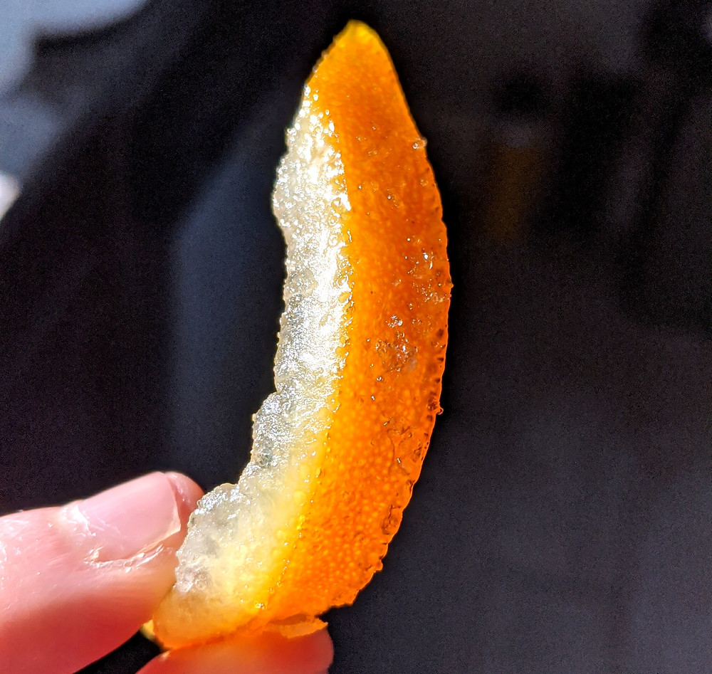 A beautiful slice of candied orange peel with the sunlight brightening the crystals