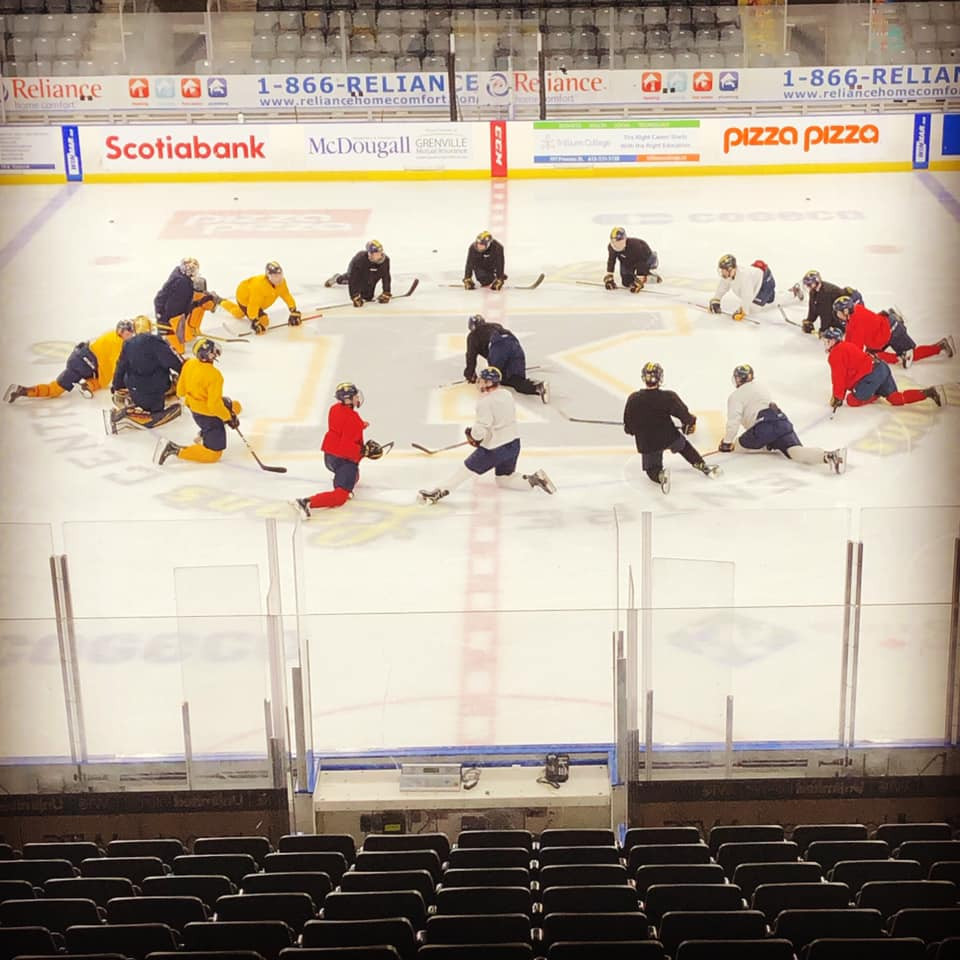 Group of hockey players warming up in a circle at the centre ice in Kingston