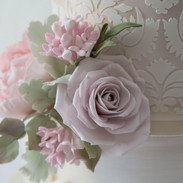 Detail of damask stencilling with sugar flowers.