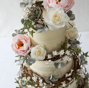 Buttercream cake with rattan wreaths and handmade sugar flowers.