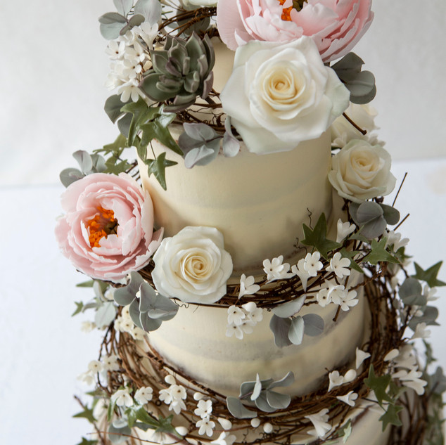 Buttercream cake with rattan wreaths and handmade sugar flowers.