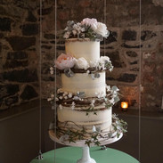 Rustic Wedding Cake with rattan wreaths of handmade sugar flowers.