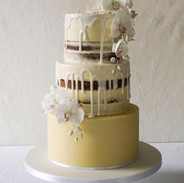 Semi naked drip wedding cake with orchid sprays.