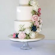An elegant wedding cake with a floral cascade of sugar flowers.
