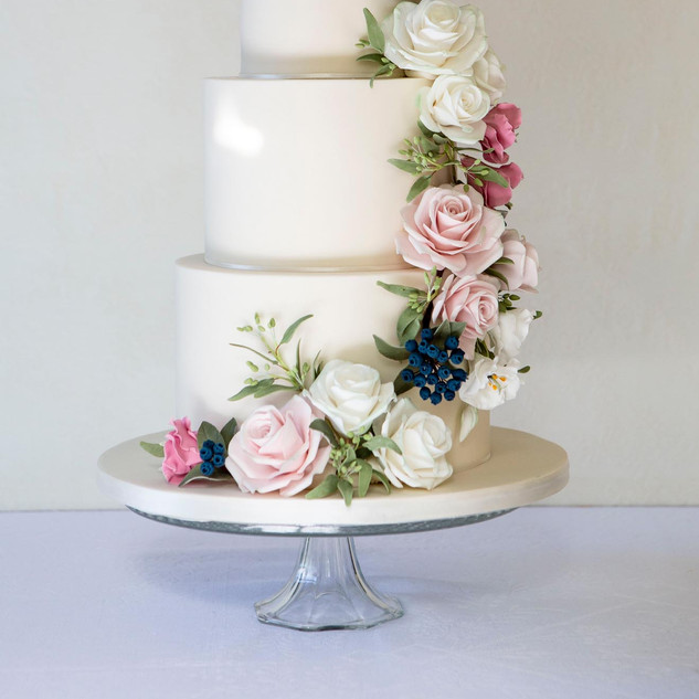 An elegant wedding cake with a floral cascade of sugar flowers.