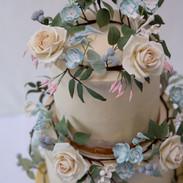 Buttercream wedding cake with handmade sugar flower wreaths.