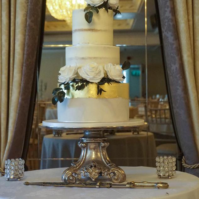 Elegant marbled and gold buttercream wedding cake set up at Bellingham Castle.