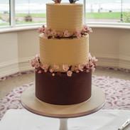Buttercream wedding cake with cherry blossom.