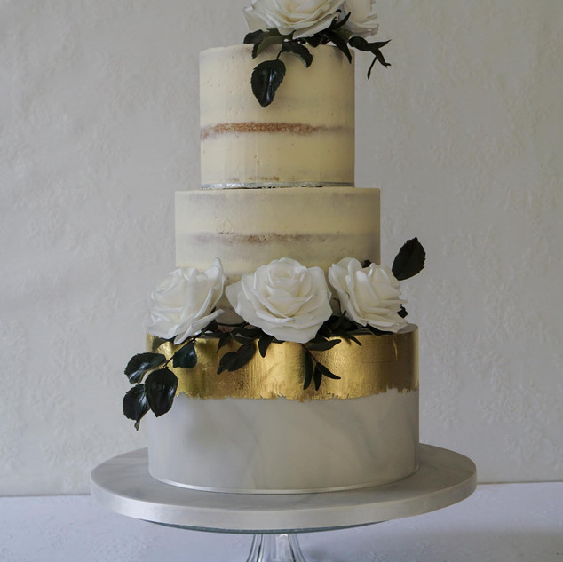 Semi naked buttercream wedding cake with marble, gold leaf and sugar roses.
