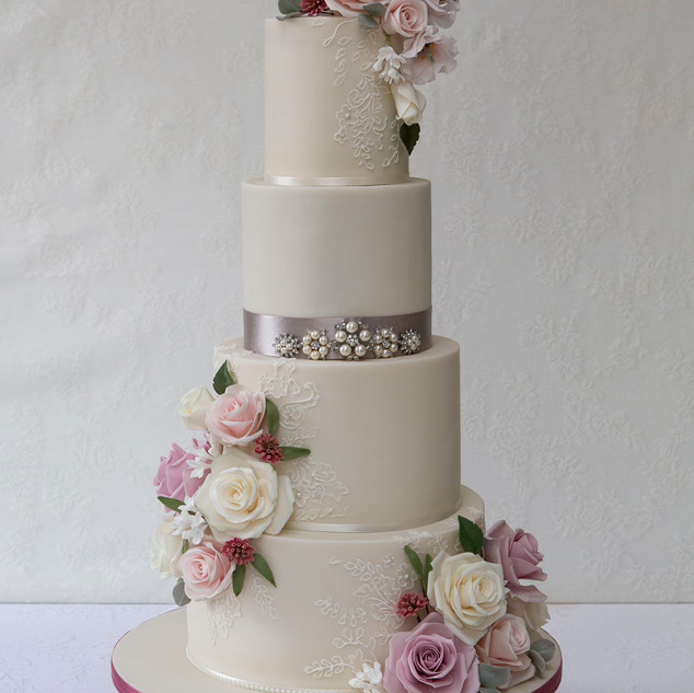 Romantic sugarpaste wedding cake with hand piiped lace detail.