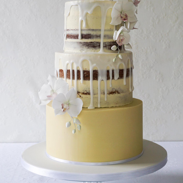 Semi naked drip cake with sugar flowers.