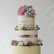 Buttercream semi naked wedding cake with handmade sugar flowers.