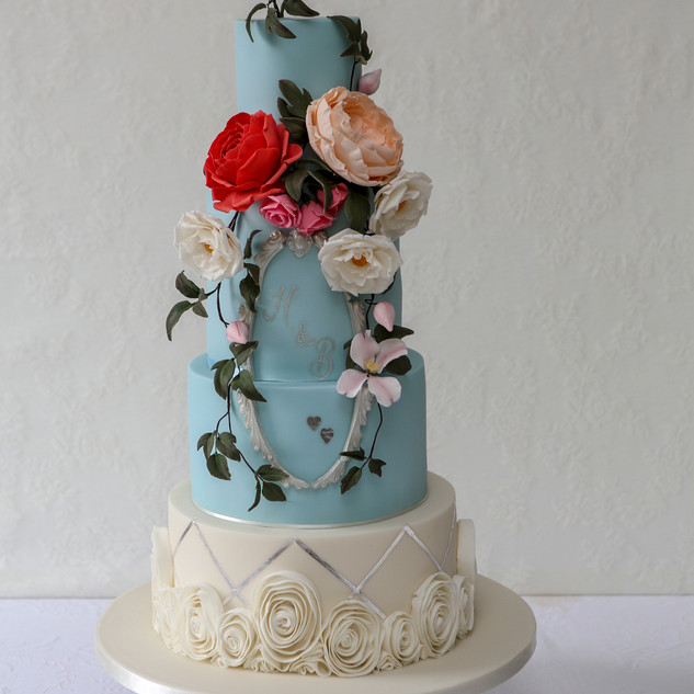 A pastel coloured wedding cake with tumbling roses and clematis.
