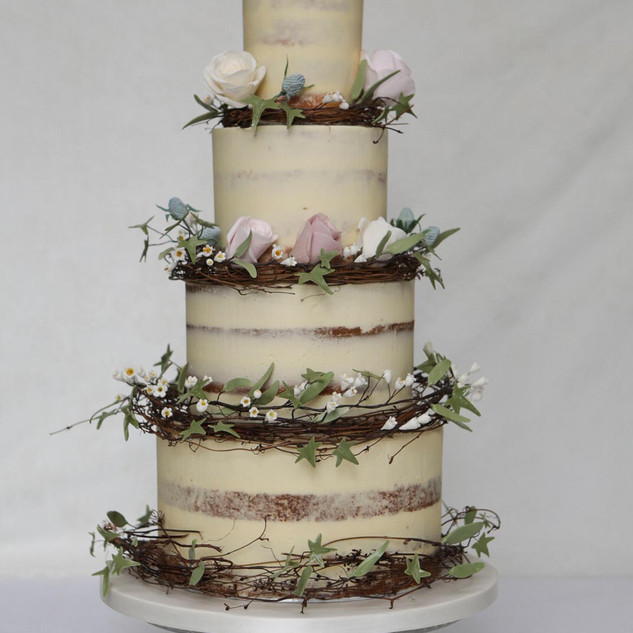 Rystic buttercream wedding cake with rattan wreaths.