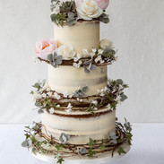 Buttercream cake with rattan wreaths and sugar flowers.