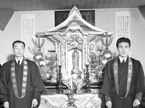 The historic beginnings of Buddhist Temple of Chicago were at Heart Mountain. Rev. Gyomay Kubose (left), formerly of Los Angeles, and apprentice Roy Higashi stand in front of the Buddhist altar in the Block 17-25 Recreation Hall used by the Higashi Hongwanji Buddhist Church in Heart Mountain on April 2, 1944. This altar was later brought to Buddhist Temple of Chicago, which was founded on Oct. 8, 1944 by Kubose. While in Chicago, Patti Hirahara will be giving a photographic presentation to the Chicago temple of the WSU Hirahara Collection pertaining to their founding minister's work. (Photo courtesy of the George and Frank C. Hirahara Collection, Washington State University Libraries MASC)
