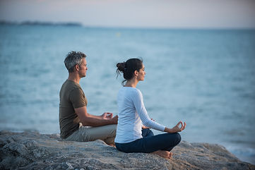 Couple practicing yoga at sunrise on the