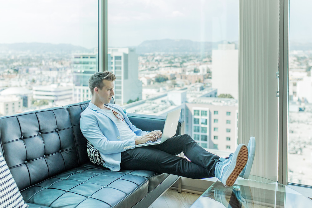 Man working remotely on couch in city