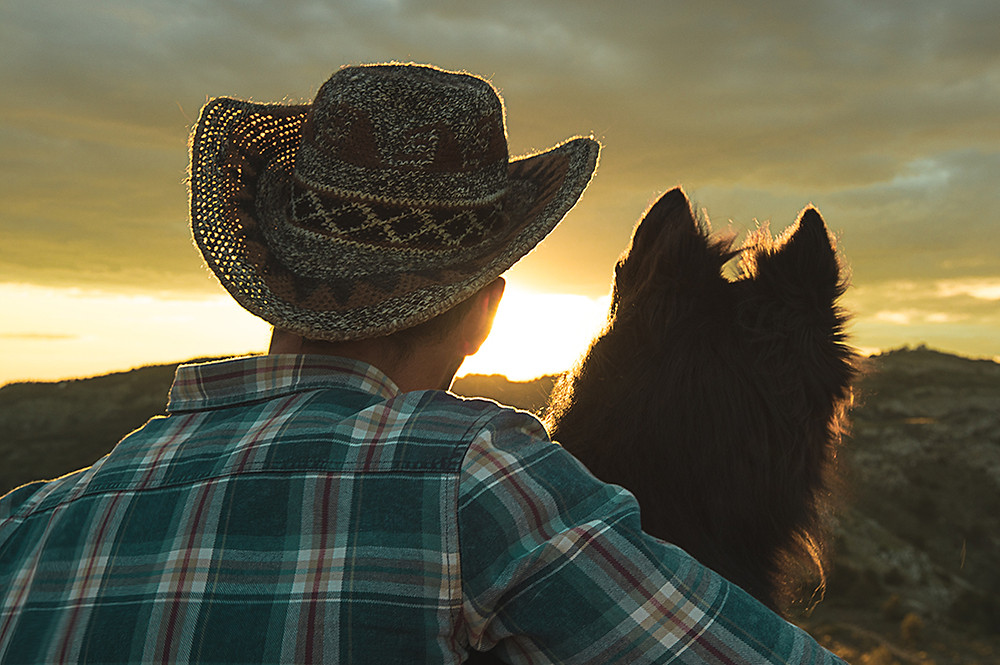 Man and his dog enjoy the sunset