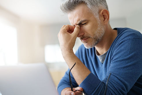 Man at home having a headache in front o