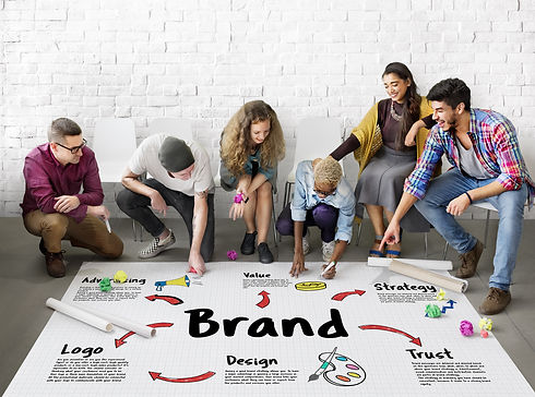 A photo of a group of young adults gathered around a brand map that shows how to develop an integrated brand
