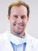 A photo of a male dentist smiling