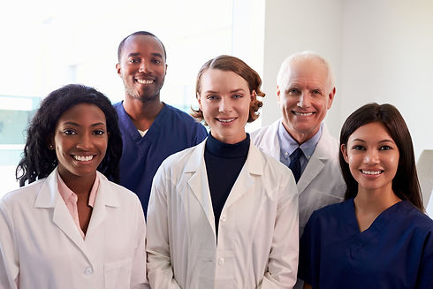 A group photo of 5 dental professionals standing side by side smiling