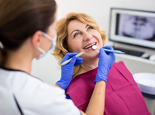 dentist with happy female patient at mod