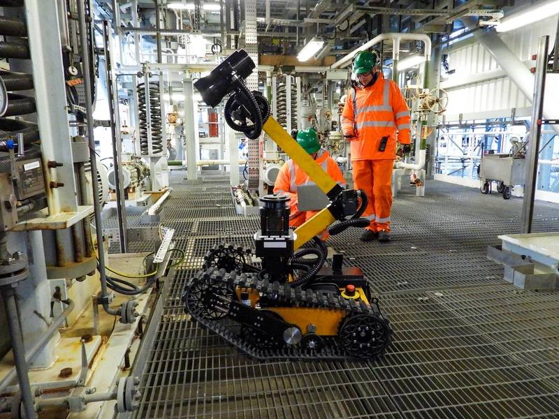 Taurob track-driven inspection robot on offshore platform with two workers