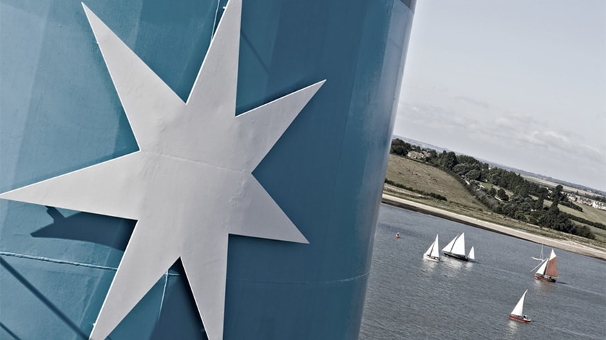 Maersk ship with the star logo and sailboats in the background