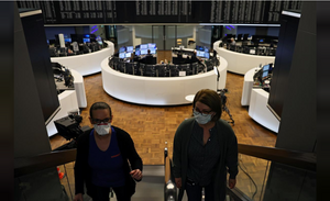 Two women with masks walk off a trading floor