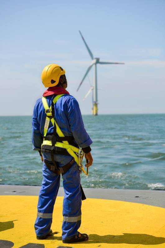 Offshore wind worker standing on a platform with a wind turbine in the background