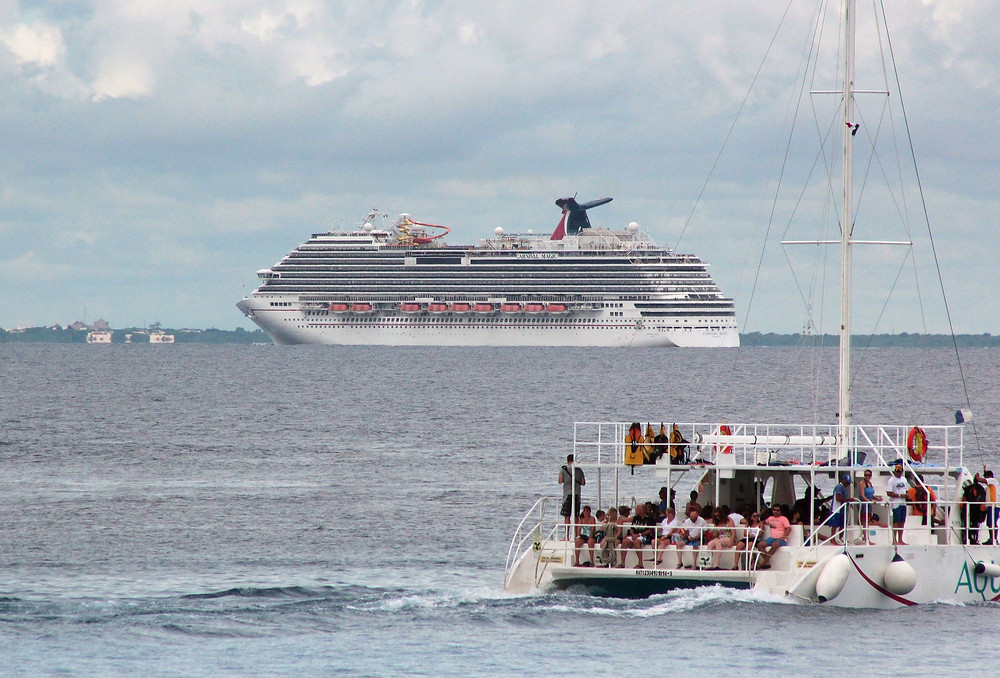 Carnival Cruise ship with a ferry in the foreground.