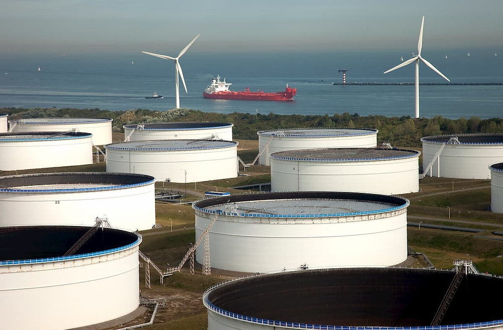 Fuel tank storage on the shore with wind turbines in the background