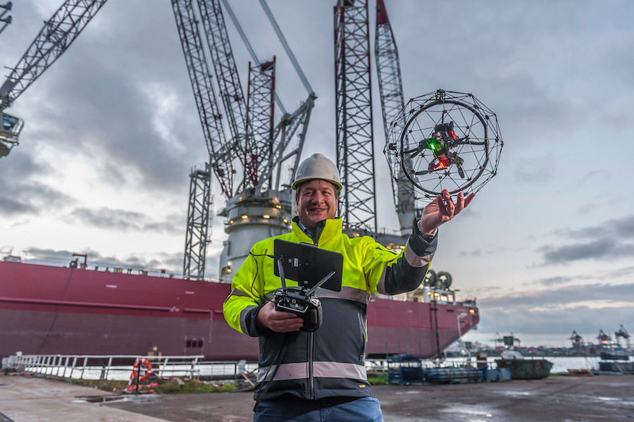 Engineer holding an inspection drone in front of a jack up vessel