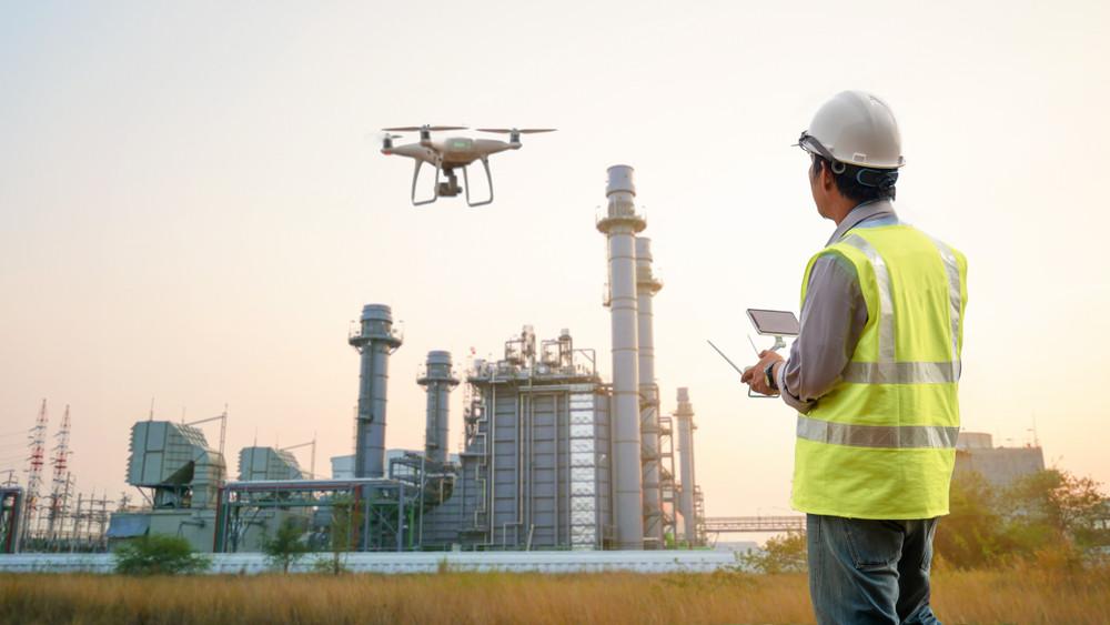 UAV with pilot near an onshore installation.