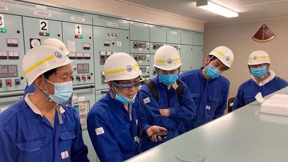 Vessel crew, one wearing AR glasses