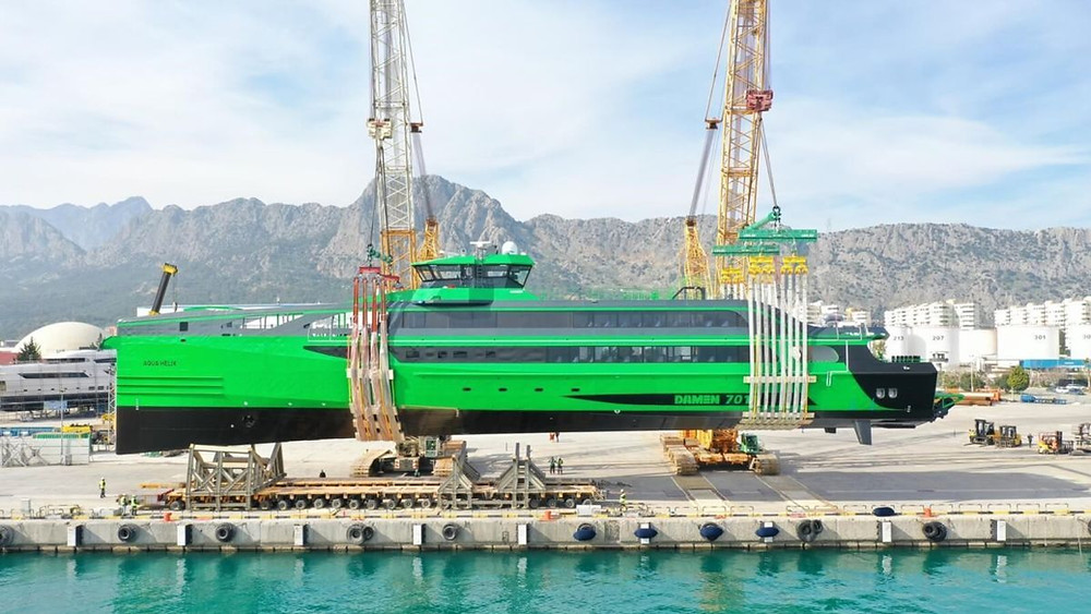 Green and black crew transfer vessel being lowered into the water with two cranes
