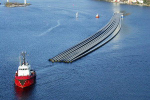 Tugboat towing pipes floating on the water.