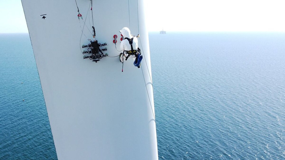 Technician on the side of a wind turbine with BladeBUG